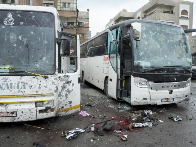 This photo, released by the Syrian official news agency SANA, shows blood soaked streets and damaged buses after a bombing in Damascus on Saturday.