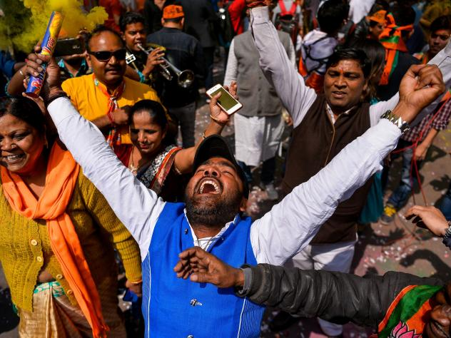 Supporters of India's Bhartiya Janata Party (BJP) celebrate elections results outside the party headquarters in New Delhi on March 11, 2017.