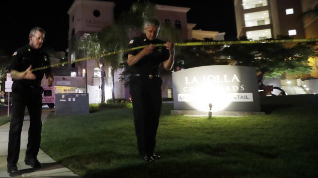 San Diego police officers work outside the scene of a shooting at an apartment complex Sunday, after a gunman opened fire on a crowd of people.