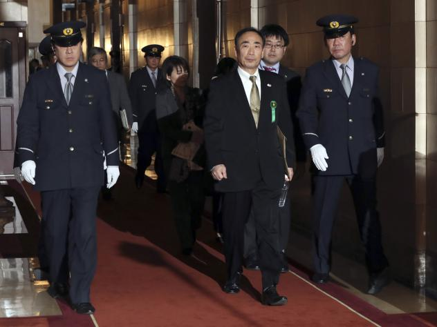 Yasunori Kagoike, center, head of an ultra-nationalistic Japanese school operator, walks through the hallway after testifying before an upper house panel at the parliament in Tokyo, on March 23.