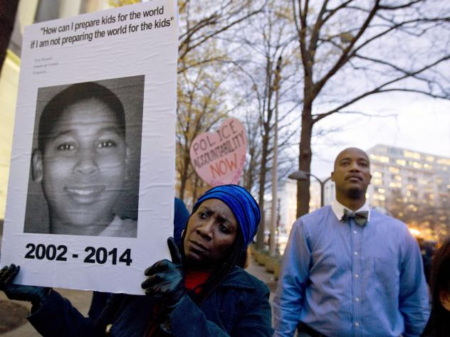 Tomiko Shine holds up a picture of Tamir Rice during a protest in Washington, D.C.