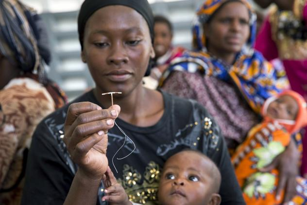 A woman in a rural area of Kenya examines an intrauterine device during a visit from a outreach team sent by a family planning organization.