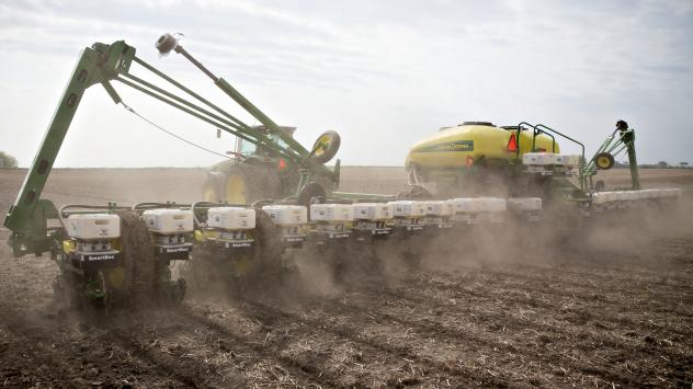 A tractor pulls a planter while distributing corn seed on a field in Malden, Ill. Two scientists agree that pesticide-laden dust from planting equipment kills bees. But they're proposing different solutions, because they disagree about whether the pestic