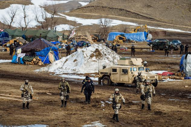 Police move through the camp of protesters against the Dakota Access Pipeline near Cannon Ball, N.D., in February. Despite months of protests by Native American tribes and environmental groups, crude oil is now flowing through the pipeline.