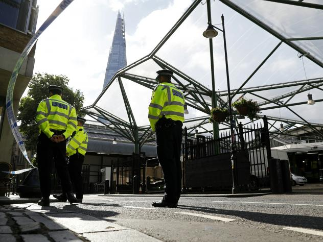 Police officers stand guard in London on Wednesday, after the security cordon was reduced. British police say they found an eighth victim of Saturday's attack.
