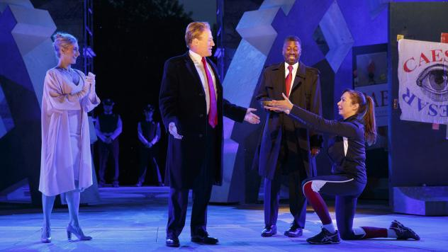 In this May 21, 2017, photo provided by The Public Theater, Tina Benko, left, portrays Melania Trump in the role of Caesar's wife, Calpurnia, and Gregg Henry, center left, portrays President Donald Trump in the role of Julius Caesar during a dress rehear
