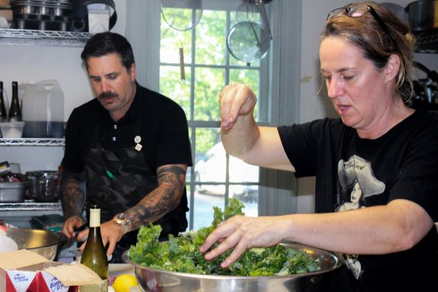 """Chef Michael Scelfo of Cambridge, Mass., left, and Lisa Carlson, who operates three food trucks in Minneapolis, collaborate on the Glynwood dinner's spelt salad with lamb tongues and hearts, and """"ugly"""" cherries, shiitakes, and kale."""