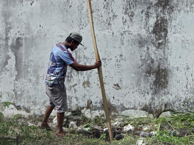 A man puts a wooden stick into a hole through which four foreign inmates escaped from Kerobokan prison in Bali Monday.