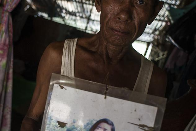 Mya Soe, 58, holds a photograph of his daughter Kyi Pyar Soe on the outskirts of Yangon, Myanmar, last year. He says he was told that his daughter was trafficked to China.