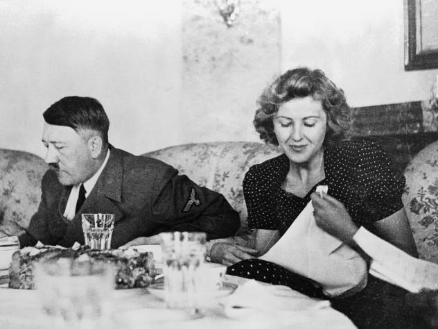 """Berlin, Germany: A candid photograph of Eva Braun with Adolf Hitler at the dining table. A new book explores the lives of six women through food, and Hitler's mistress is a startling inclusion. But what Braun ate reflected a """"perpetual enactment of her o"""