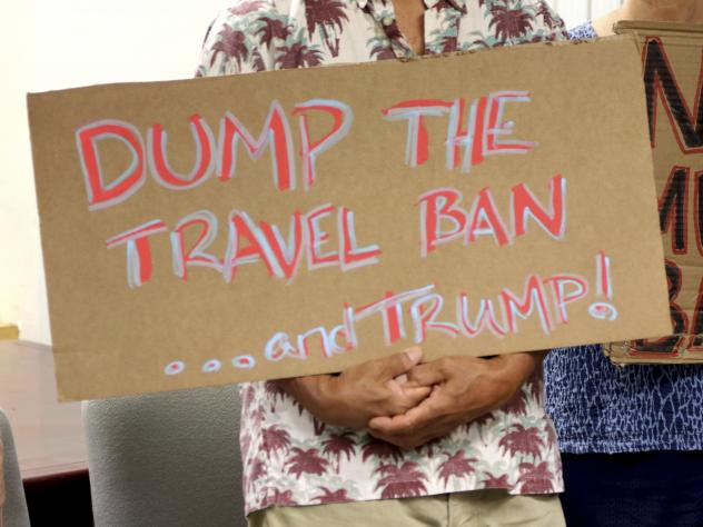 Critics of President Trump's travel ban hold signs during a news conference with Hawaii Attorney General Douglas Chin on June 30 in Honolulu.