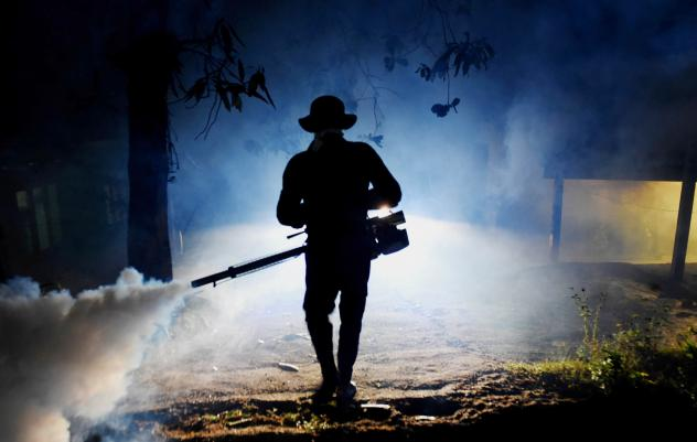 A worker sprays a neighborhood on the outskirts of Colombo in Sri Lanka with a fog used to ward off mosquitoes. The country is facing an outbreak of dengue fever, a mosquito-borne disease.