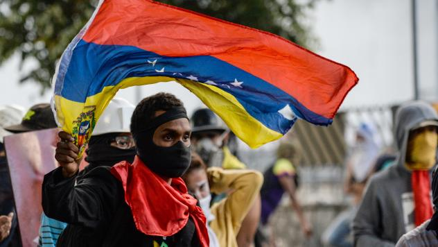 An anti-Maduro demonstrator waves the Venezuelan flag at a protest in the capital, Caracas, on Wednesday. The government banned such demonstrations nationwide for the next five days, as the country approaches a Sunday vote on delegates for Maduro's const
