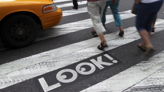 """Pedestrians walk past a """"Look!"""" sign on the crosswalk at the intersection of 42nd St. and 2nd Ave. in New York. Cities all over the country are looking for ways to get pedestrians to pay more attention."""