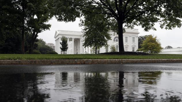 The White House is seen reflected in a rainwater puddle on Friday, July 28, 2017 — amid very stormy times in Washington, D.C.