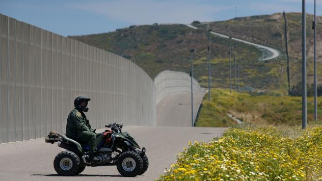 A Border Patrol agent keeps watch over the U.S.-Mexico border fence just south of San Diego earlier this year. The Department of Homeland Security announced Tuesday that it would waive environmental and other laws to expedite its construction of barriers