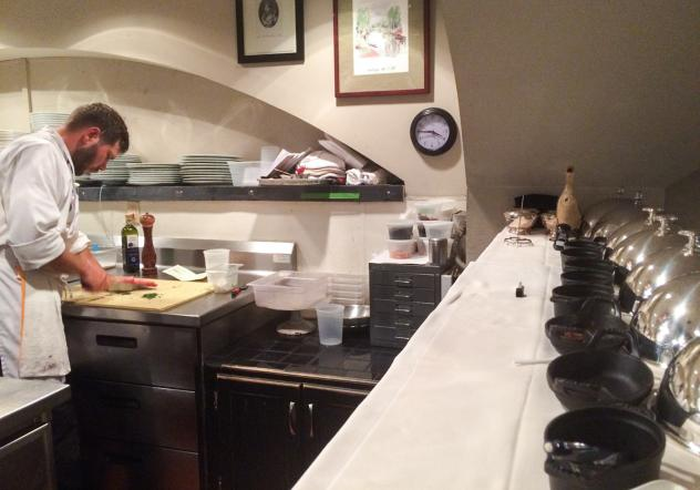David Uzzell at work in the kitchen at Marcel's. Uzzell has a written list of daily tasks from chef and owner Robert Wiedmaier at his station, and his ever-present notepad and pencil on the shelf above serves as communication tools for more specific inst