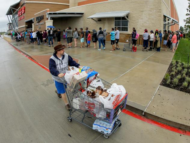 People in Richmond, Texas, line up to gain entrance to a grocery store after it opened for the first time in several days due to Tropical Storm Harvey.