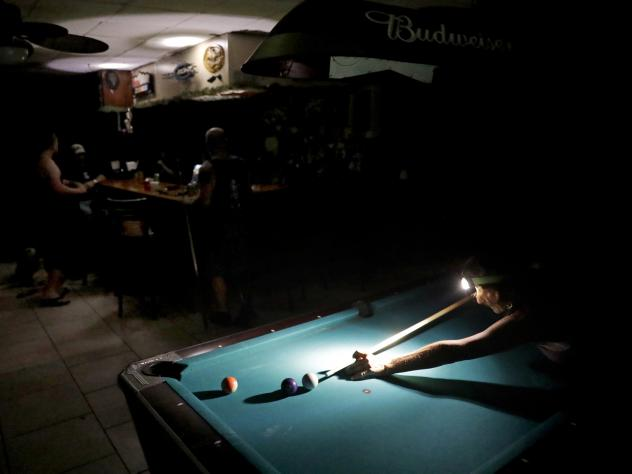 Playing pool during a power outage from Hurricane Irma, Lisa Borruso used a headlamp to line up a shot at Gators' Crossroads in Naples, Fla., Monday. Millions of people had their power knocked out by the storm — and some outages will continue for days.