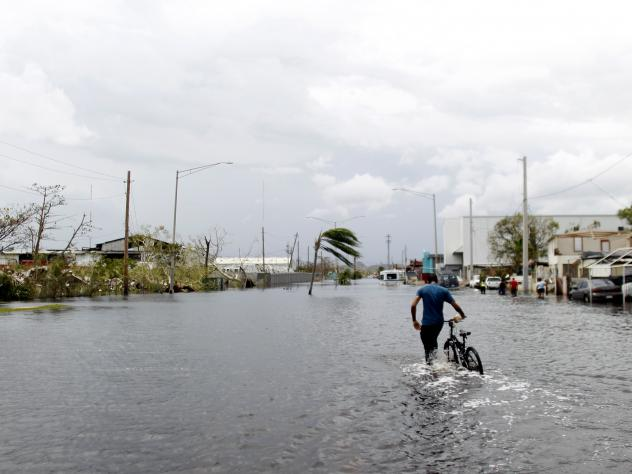 A man pushes his bicycle through a flooded street in Cataño, Puerto Rico, on Friday. Hurricane Maria drenched many spots on the island with about 20 inches of rain.
