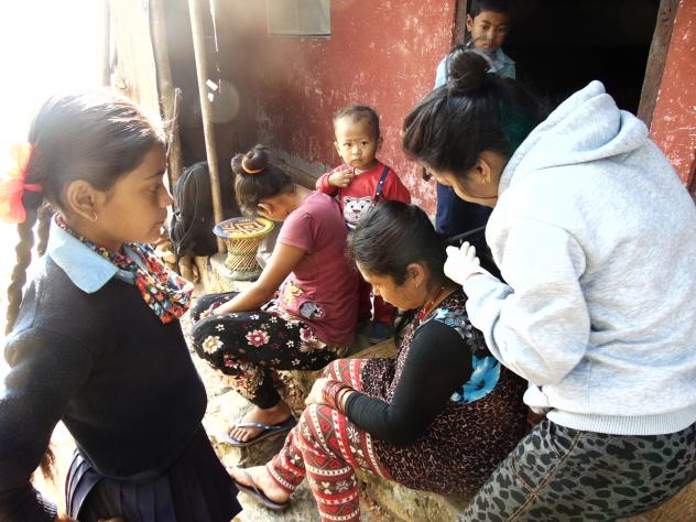 A public health worker in Nepal takes a sample of hair for mercury analysis.