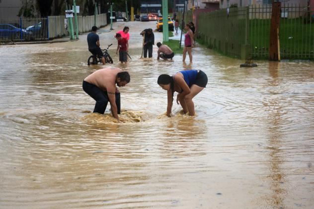 Jomar Maldonado (right) and Abigail Diaz mop up floodwaters in their home.