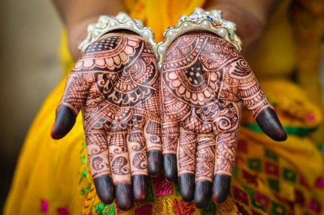 An Indian bride's hand decorated with henna tattoos.