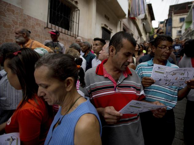 People read voting instruction as they wait to cast their ballots for regional elections outside a polling station in Caracas, Venezuela, on Sunday.