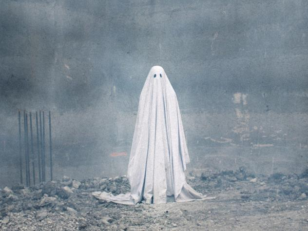 A ghost stands in the ruins of a demolished building in a scene from the film <em>A Ghost Story.</em>