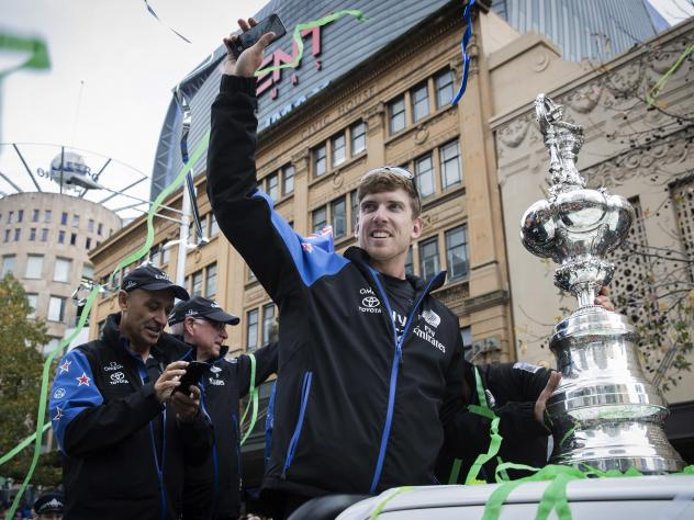 Team New Zealand America's Cup helmsman Peter Burling waves during a welcome home parade through the streets of Auckland, New Zealand, in July. This month, he'll begin a round-the-world race with eight team members.