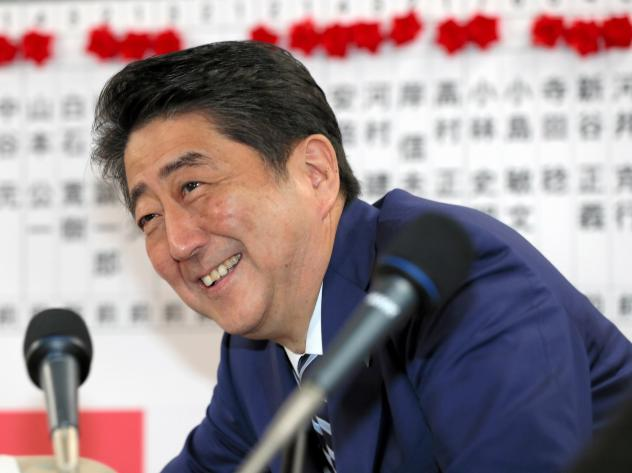 Japanese Prime Minister and ruling party president Shinzo Abe smiles during a press conference after the general election Sunday in Tokyo.
