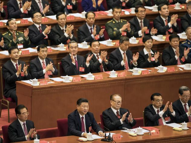 """Applause rained down for China's President Xi Jinping on Tuesday, as the Communist Party of China adopted his """"thought."""" Xi (bottom center) was flanked by former presidents (from left) Hu Jintao and Jiang Zemin, along with Premier Li Keqiang."""