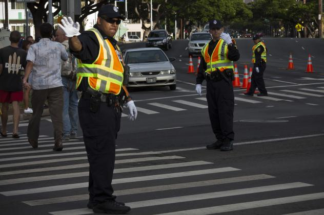 Honolulu police officers direct traffic at an intersection. Honolulu is the first major U.S. city to ban texting while walking in a crosswalk.