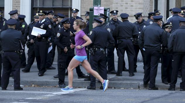 A runner moves past a group of police officers gathered near the finish line of the New York City Marathon on Nov. 6, 2016. Authorities are increasing the number of officers and other law enforcement personnel for this year's race, in the wake of an Tues