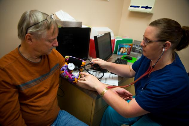 Emily Blair, a medical assistant at the Colon, Stomach and Liver Center in Lansdowne, Va., takes a blood pressure reading for Robert Koenen. New guidelines say that patients should have their arm resting on a surface while taking a reading and both feet