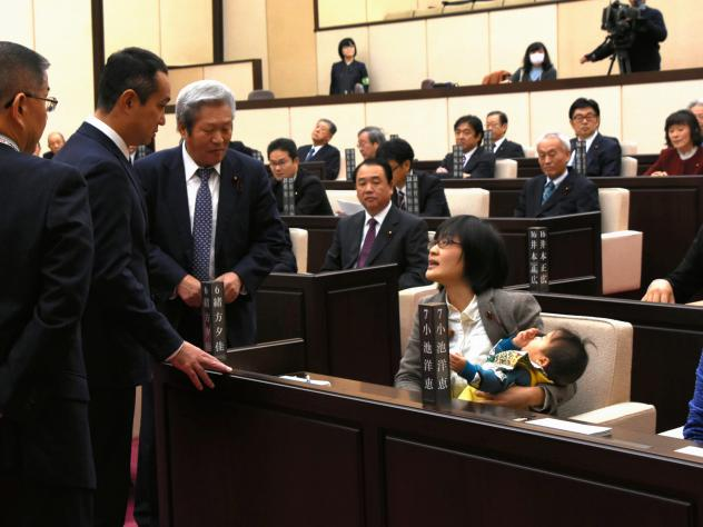 Lawmakers in the Kumamoto Municipal Assembly talk with member Yuka Ogata, who brought her infant son to work.