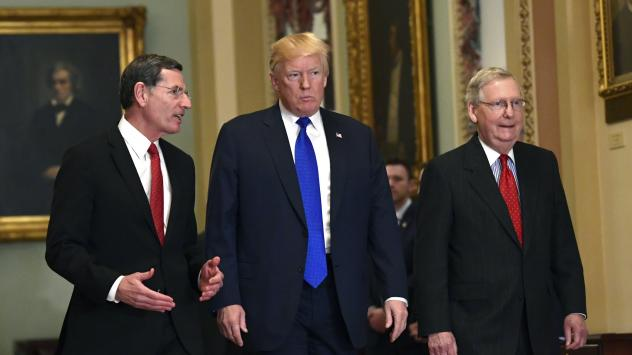 President Trump at a Senate GOP lunch with Sen. John Barrasso, R-Wyo. (left), and Senate Majority Leader Mitch McConnell, R-Ky., on Tuesday, where he talked with several holdouts on the tax bill about measures to bring them on board.