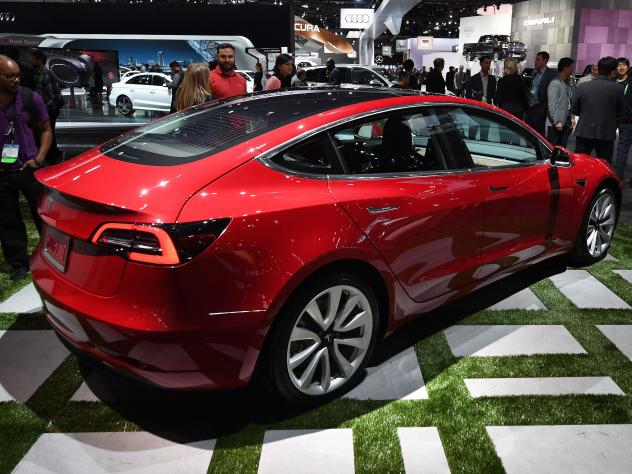 The new Tesla Model 3 is displayed at the 2017 LA Auto Show. The company has struggled to meet its goal of producing thousands of the vehicles per week.