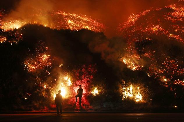 Motorists on Highway 101 watch flames from the Thomas fire leap above the roadway north of Ventura, Calif., on Wednesday.