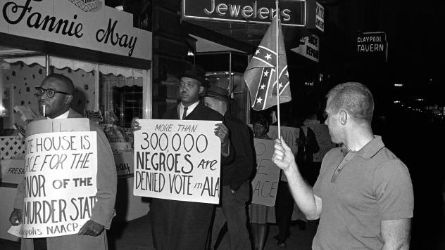 """A demonstrator carries a sign that says """"More than 300,000 Negroes are Denied Vote in Ala"""" to protest then-Alabama Gov. George Wallace's visit to Indianapolis in 1964. The word """"Negro"""" was widely used to describe black people in the U.S. during the early"""