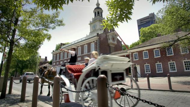 A tour guide on a horse-drawn carriage points outside of Independence Hall in Philadelphia in 2007. One of the city's two horse-drawn carriage companies is closing down and transferring its animals to the city.