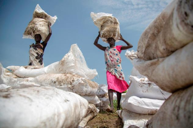 Women carry sacks of food, airdropped by the World Food Programme in Jonglei, South Sudan, July 2017.