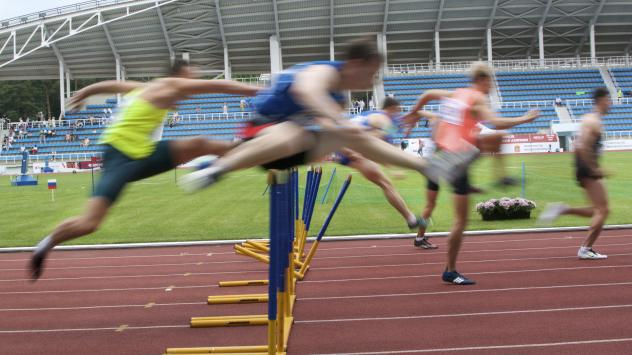 Athletes compete in the 110-meter hurdles semifinal run during the national track and field championship in Moscow in July 2017.