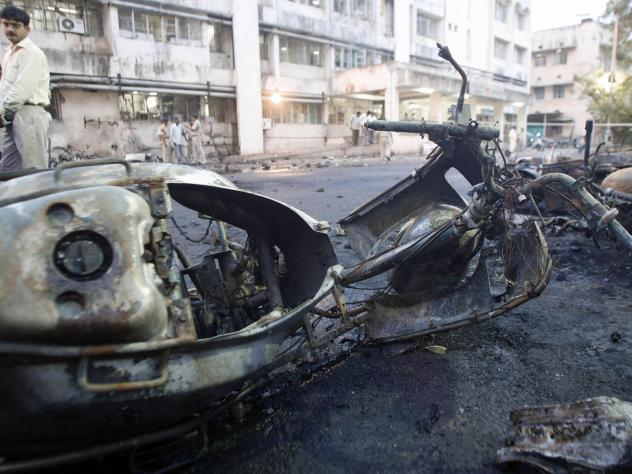 """A journalist looks at the remains of motorcycles at a bomb blast site outside a hospital in Ahmedabad on July 27, 2008. The bombing is one of several attributed to Abdul Subhan Qureshi, known as """"India's Bin Laden."""""""
