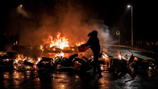 Striking prison guards light a fire as they demonstrate in front of Villefranche-sur-Saone prison on Monday as part of a nationwide movement to call for improved safety and wages.