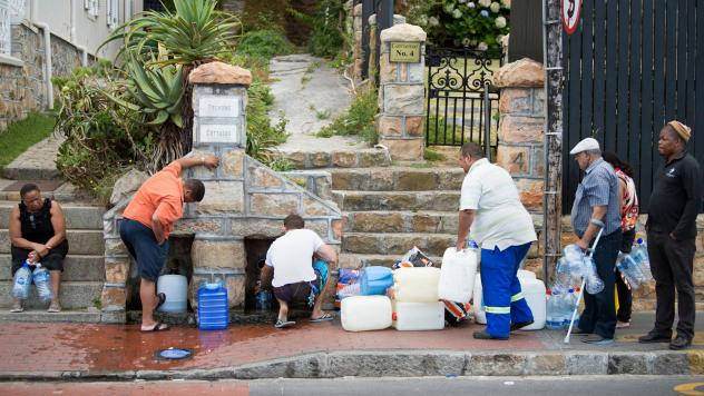 People collect drinking water from pipes fed by an underground spring last week in Cape Town. Next month, the city will slash its individual daily water consumption limit to 13.2 gallons, the mayor said, as the city battles its worst drought in a century