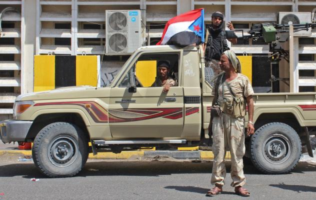 Supporters hop on a tank operated by Southern Transitional Council separatists, as they patrol near the presidential palace in Aden on Tuesday.
