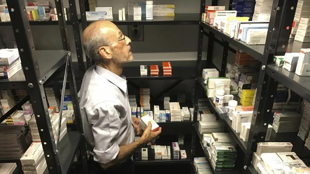 A volunteer from the non-profit Accion Solidaria organizes imported medicines alphabetically, in a store room in Caracas, Venezuela, last April. The Pharmaceutical Federation of Venezuela estimates the country is suffering from an 85 percent shortage of