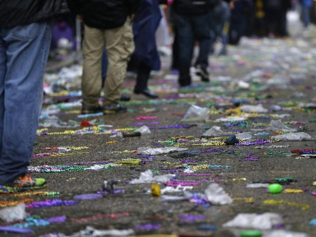 A 'gutter buddy' blocks Mardi Gras detritus from a storm drain opening near the parade route in New Orleans.