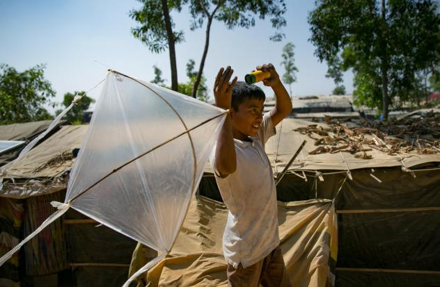 Children fly kites along a ridge in the camp. Many of the refugees fled Myanmar with only a few possessions. For some kids homemade kites are the only toys they have.